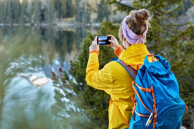 Back view of woman traveler takes photo on camera of modern cell phone, captures scenic view near mountain lake, has road trip