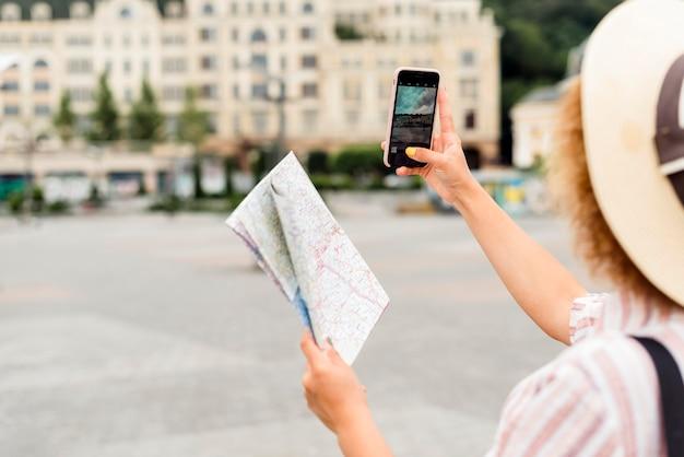 Вид сзади женщина, путешествующая одна с картой
