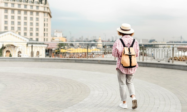 Back view woman traveling to a new place with copy space