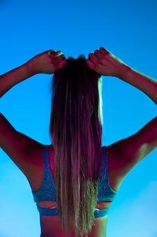Punto di vista posteriore della donna che lega i suoi capelli