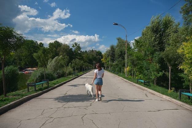 Вид сзади женщина гуляет со своей собакой в парке