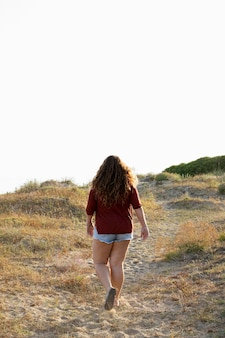 Back view of woman walking outdoors in nature