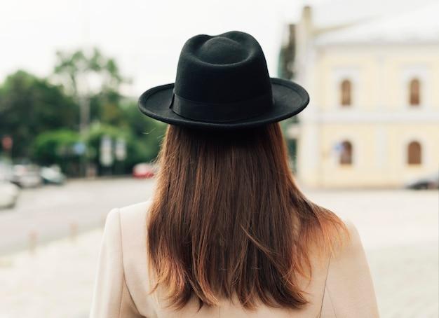 Вид сзади женщина в черной шляпе