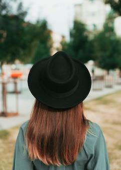 Vista posteriore della donna che indossa un cappello nero in autunno
