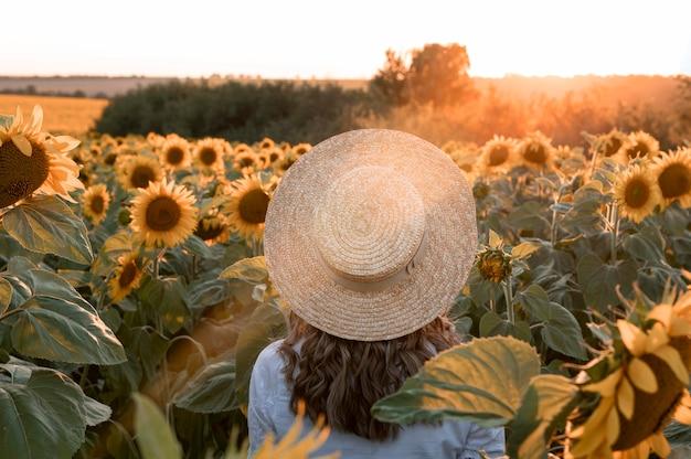 Back view woman wearing hat in field