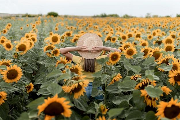 屋外の帽子をかぶっている背面図女性