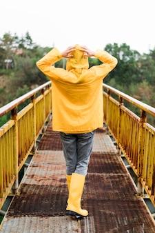 雨の服を着て背面図女性