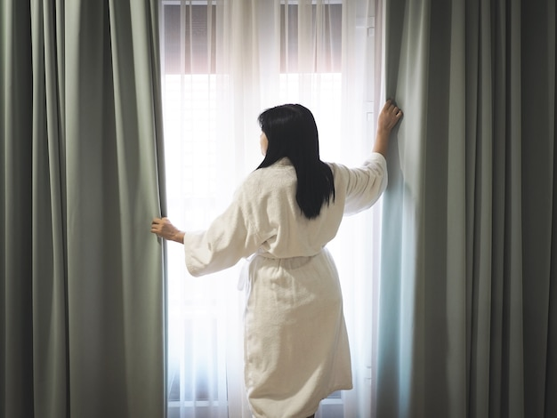 Back view of woman wearing white bathing gown and opening curtains window bedroom in early morning