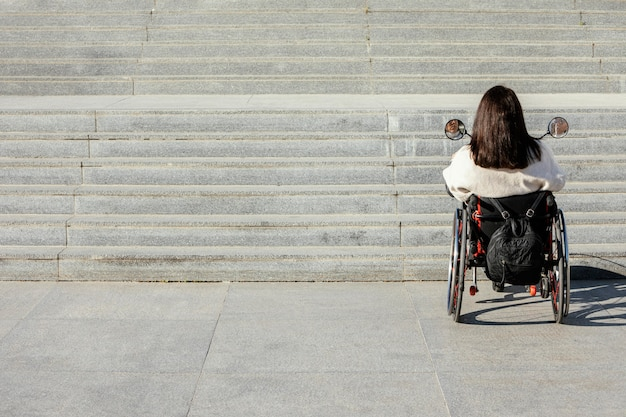 Back view of woman in a wheelchair approaching stairs