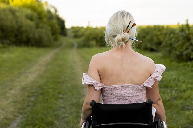Back view of woman in wheelchair outdoors