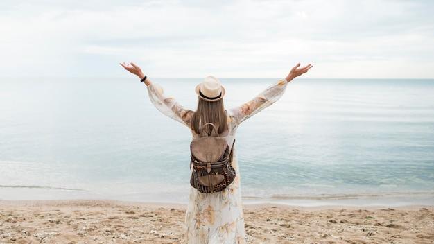 Вид сзади женщина с рюкзаком, наслаждаясь отпуск