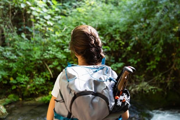 Vista posteriore della donna con lo zaino ad esplorare la natura