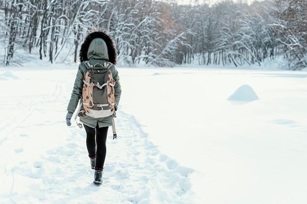 Donna vista posteriore con zaino in giornata invernale