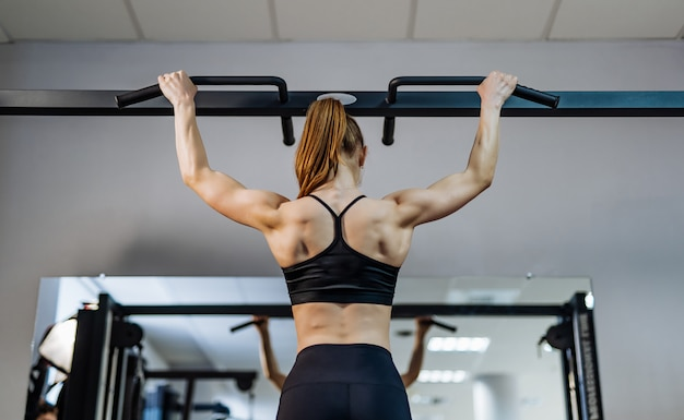 Back view of a woman with hair in pony tail doing workout tightening on bar in gym.