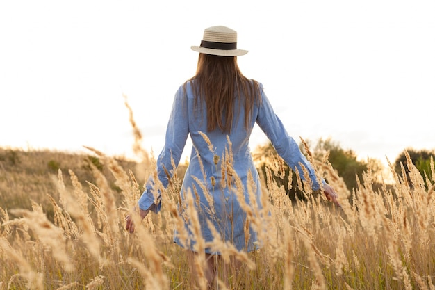 Back view of woman with hat posing through the fields