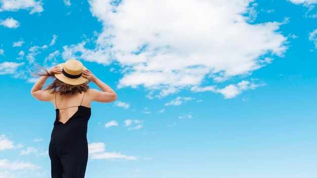 Back view of woman with hat and sky with clouds