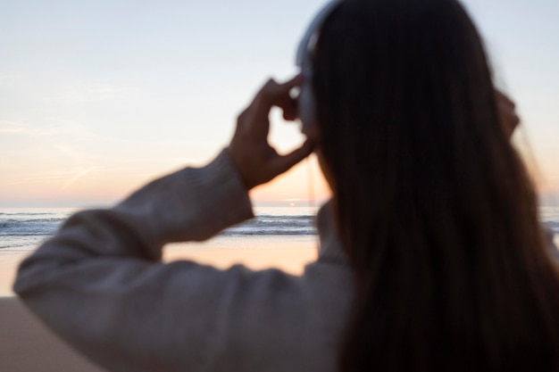 Back view of woman with headphones by the beach