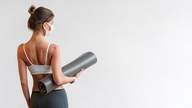 Back view of woman with medical mask holding yoga mat