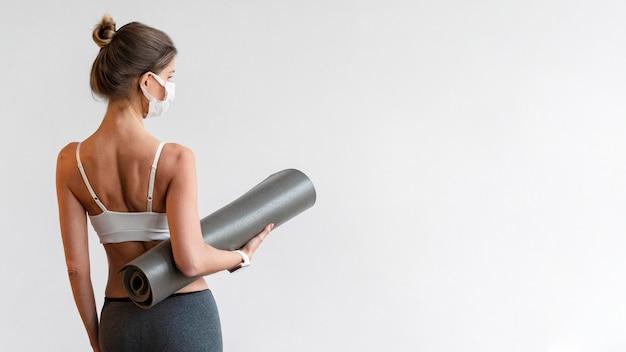 Vista posteriore della donna con maschera medica tenendo la stuoia di yoga