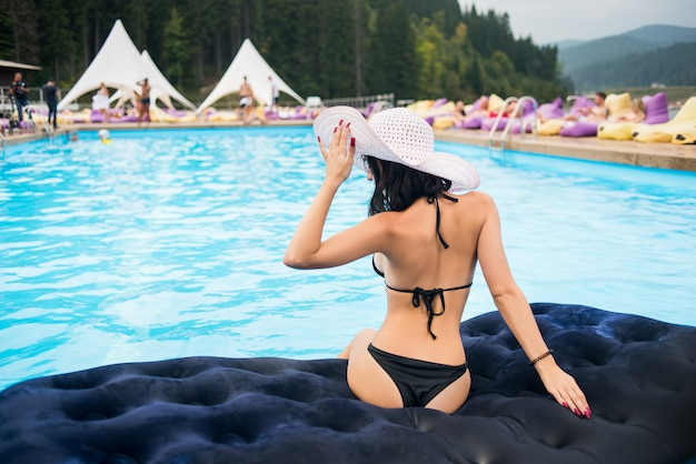 Back view woman with perfect figure in a black bikini and hat sit on a mattress in the swimming pool