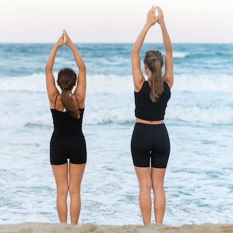 Back view of women doing yoga on the beach
