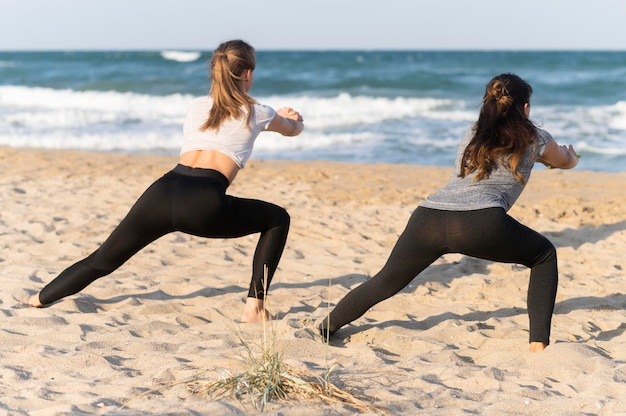 Back view of women exercising on the beach