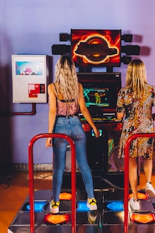 Back view women playing dancing arcade