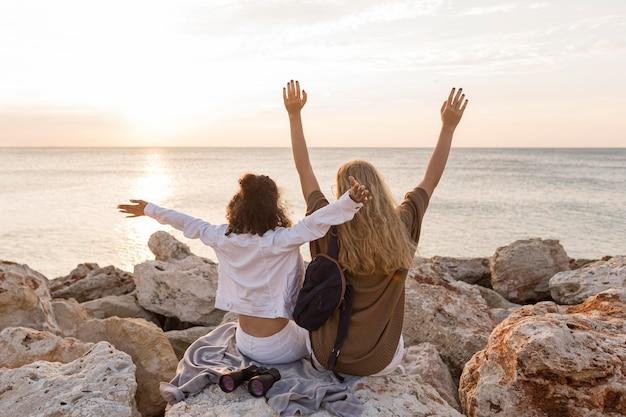 Donne di vista posteriore che si siedono sulla roccia