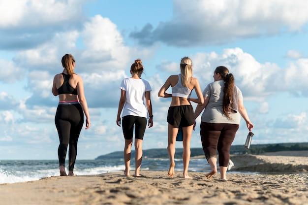 Donne di vista posteriore che camminano sulla riva