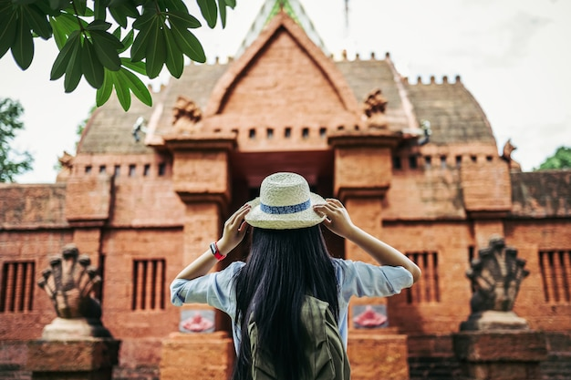 Back view of young asian backpacker woman with black long hair wearing hat standing ant looking to beautiful ancient site or old temple during traveling on vacation