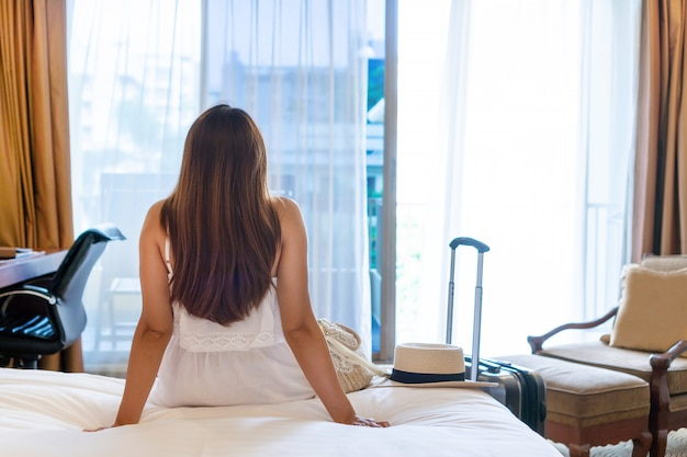 Back view of young asian traveler in white dress relaxing looking through a window in hotel room after arrival with luggage in the foreground.