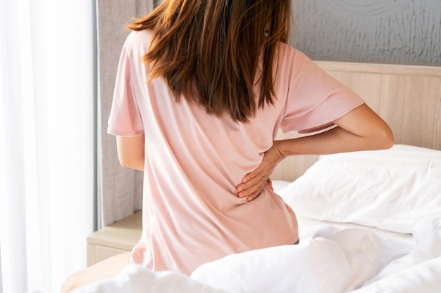 Back view of young asian woman suffering from backache on bed in the morning.