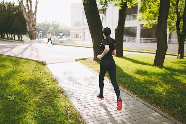 Vista posteriore giovane ragazza bruna atletica in uniforme nera e allenamento con berretto, facendo esercizi sportivi e correndo, guardando dritto sul sentiero nel parco cittadino all'aperto