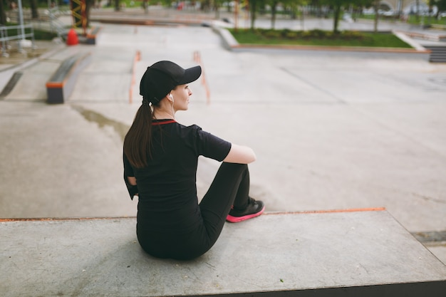 Back view young athletic brunette woman in black uniform and cap with headphones listening to music resting and sitting before or after running, training in city park outdoors