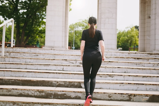 Back view of young athletic strong brunette woman in black uniform and cap doing sport exercises, warm-up before running climbing on stairs in city park outdoors