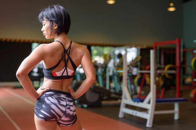 Back view of young beautiful asian woman thinking at the gym