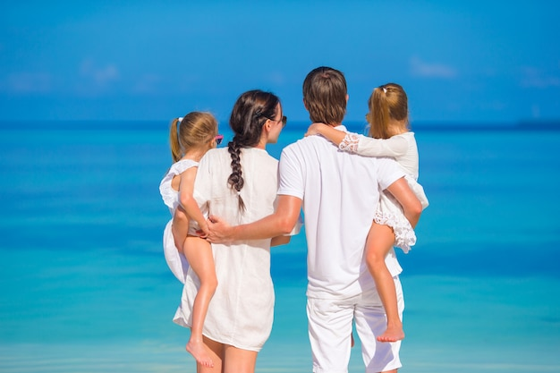 Back view of young beautiful family on white tropical beach
