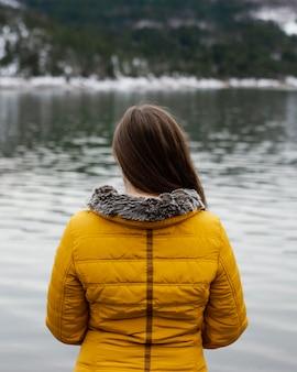 自然の中で若い美しい女性の背面図