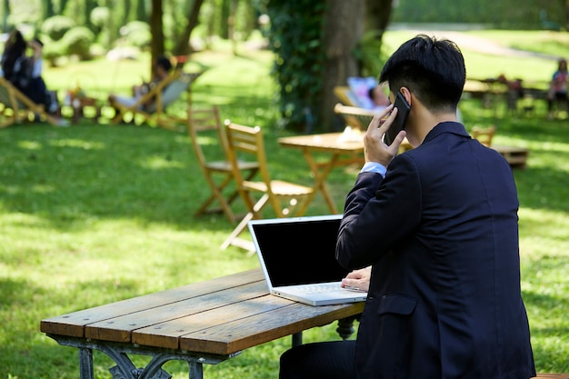 Back view of a young businessman sitting in the garden for work