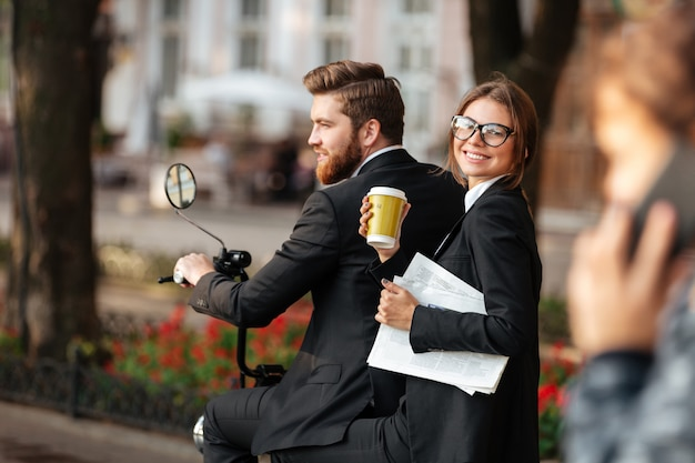 Back view of young carefree elegant couple rides on motorbike