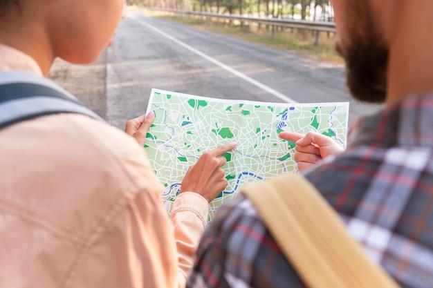 新しい目的地の地図をチェックしている若いカップルの背面図