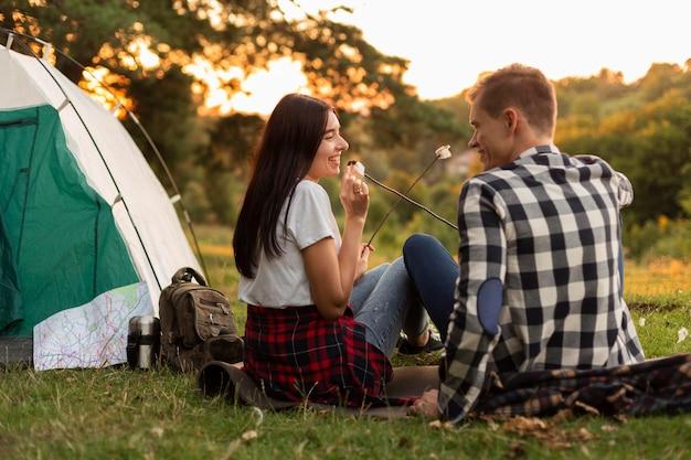 一緒に自然を楽しんでいる若いカップルの背面図