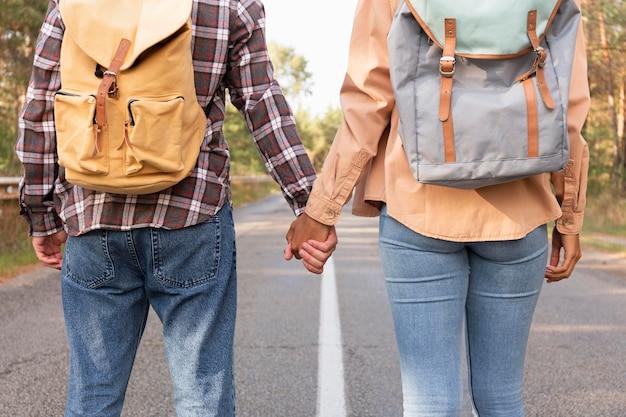 手をつなぐ若いカップルの背面図