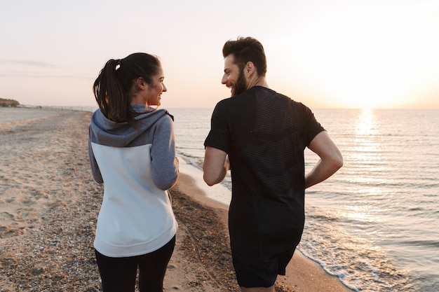 Back view of a young couple jogging together on a beach