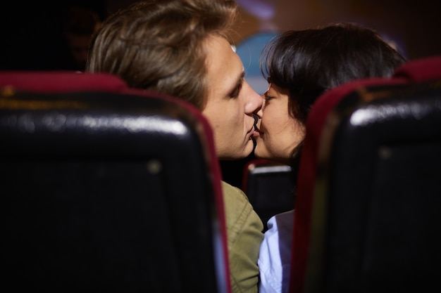 Back view at young couple kissing in cinema while enjoying romantic date, shot from between seats in dark room, copy space