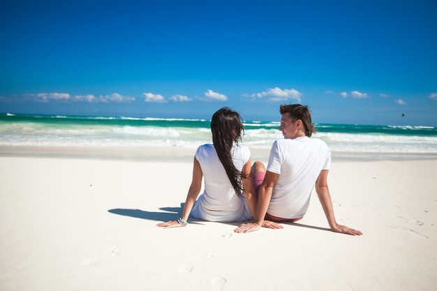 Back view of young couple in love sitting at tropical white beach