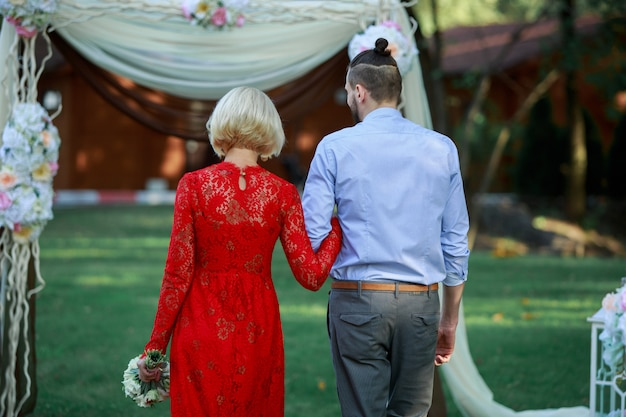 Back view of young couple in love walking hand in hand at the green spring park. stylish woman in long red dress and man walking outdoors near wedding arch . romantic date on the nature. wedding day