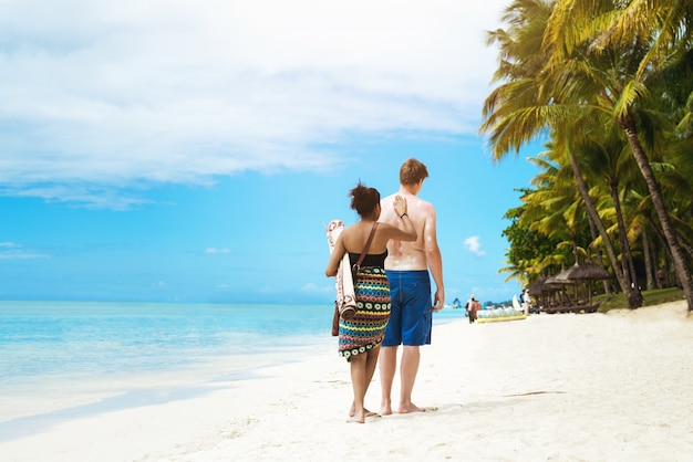 Back view of young couple sunbathing on bright beach