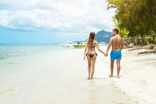 Back view of young couple in swimwear holding hands