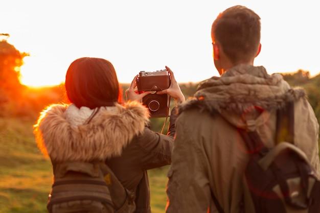 Вид сзади молодая пара фотографирует на отдыхе